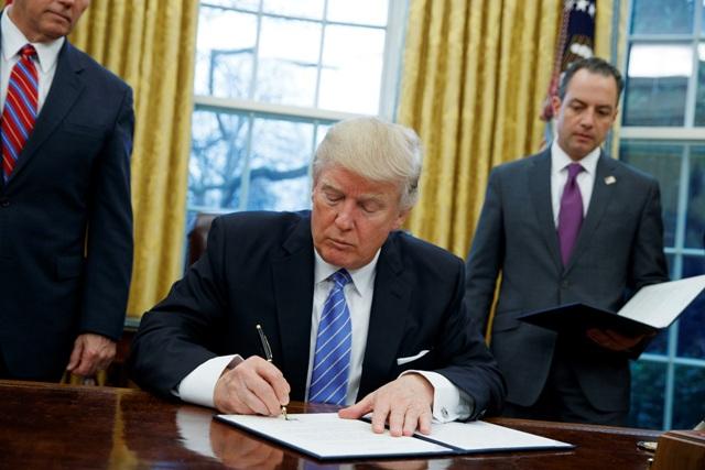 Americký prezident Donald Trump podpisuje výkonné nariadenie o odstúpení USA od Dohody o transpacifickom partnerstve (TPP) s 11 štátmi Tichomoria v Oválnej pracovni Bieleho domu vo Washingtone