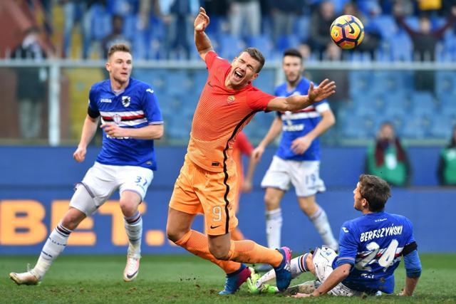 Futbalista AS Rím Edin Džeko (uprostred) a hráč Sampdorie Poliak Bartosz Bereszynski bojujú o loptu v nedeľňajšom zápase 22. kola talianskej Serie A, Sampdoria Janov - AS Rím