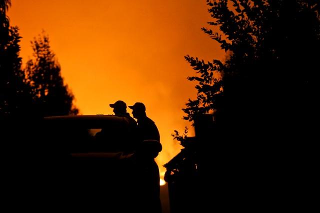 Muži odchádzajú na malom nákladnom aute po evakuácii pred lesným požiarom, ktorý ohrozuje mesto Portezuelo v Čile 30. januára 2017