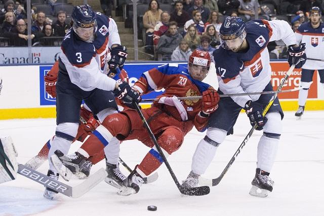 Ruský hráč Danila Kvartaľnov (v strede) v zajatí Slovákov Martina Bodáka (vľavo) a Mária Grmana (vpravo) v zápase B-skupiny Rusko - Slovensko na MS hráčov do 20 rokov v hokeji v kanadskom Toronte 31. decembra 2016
