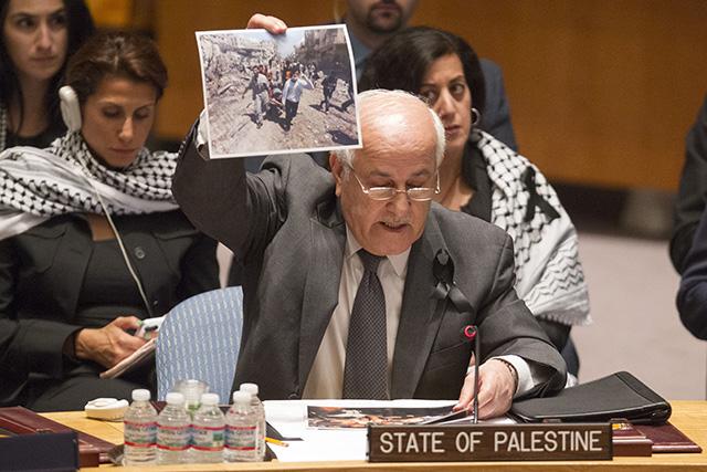 Palestínsky pozorovateľ pri OSN Rijád Mansúr ukazuje fotografiu z bojov medzi medzi Izraelom a militantmi Hamasu, ktorí kontrolujú pásmo Gazy počas zasadnutia Bezpečnostnej rady OSN