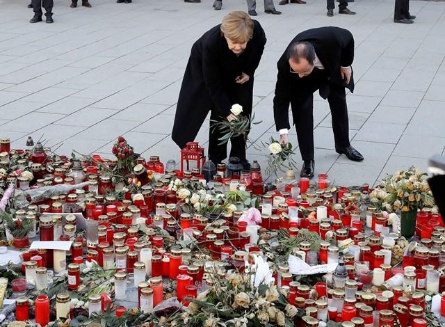 Nemecká kancelárka Angela Merkelová (vľavo) a francúzsky prezident  Francois Hollande kladú kvety na pamiatku obetí decembrového teroristického útoku na Námestí Breitscheidplatz v Berlíne