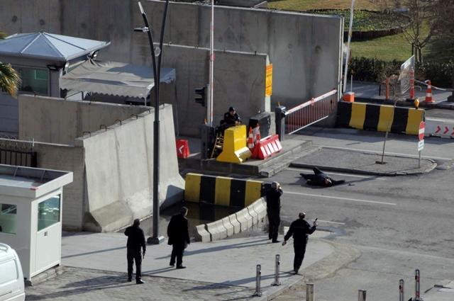 Na snímke zastrelený útočník a policajti počas akcie