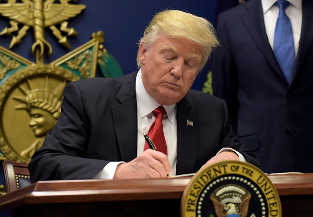 Na snímke prezident Trum podpisuje dokument
