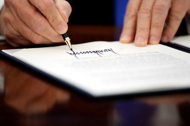 Na snímke prezident Trump podpisuje dokument