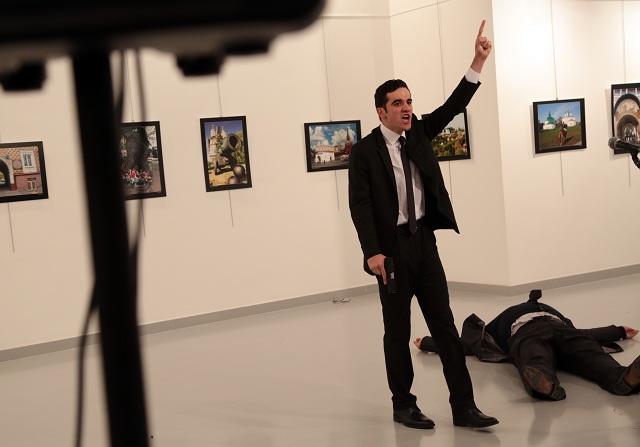 Na archívnej snímke muž gestikuluje vedľa tela postreleného ruského veľvyslanca v Turecku Andreja Karlova v galérii 19. decembra 2016 v Ankare. Neznámy útočník vystrelil počas otvorenia fotografickej výstavy v tureckej metropole Ankara na ruského veľvyslanca Andreja Karlova. S odvolaním sa na svojho fotoreportéra o tom informovala agentúra AP