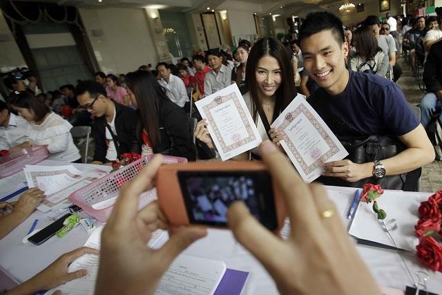 """Na snímke novomanželia ukazujú svoj sobášny list v Bangkoku na Valentína v utorok 14. februára 2017. Thajská vláda práve v utorok na Valentína rozdáva prípadným budúcim matkám pilulky, ktoré nazýva """"veľmi čarovné vitamíny"""". Vláda tak chce zvýšiť klesajúcu pôrodnosť v krajine"""