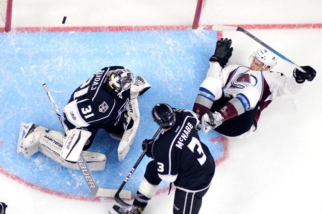 Hokejista Colorada Avalanche  Blake Comeau (vpravo), brankár Los Angeles Kings Slovák Peter Budaj (vľavo) a jeho spoluhráč Brayden McNabb v zápase zámorskej hokejovej NHL Los Angeles Kings - Colorado Avalanche