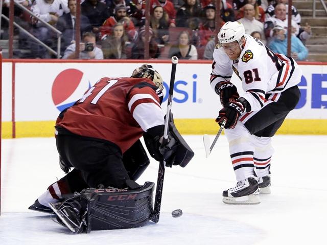 Hokejista Chicaga Blackhawks Slovák Marián Hossa (vpravo) strieľa gól brankárovi Arizony Coyotes Mikeovi Smithovi v zápase zámorskej hokejovej NHL