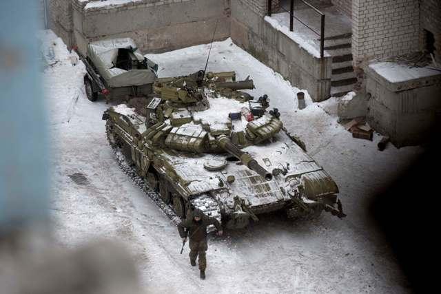 Ukrajinský vojak zoskakuje z tanku medzi domami na sídlisku v meste Avdijivka na východe Ukrajiny