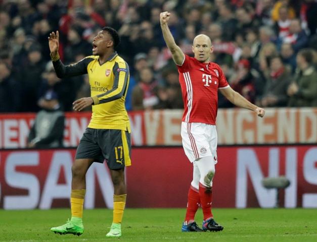 Na snímke vpravo hráč Bayernu Arjen Robben oslavuje gól, vľavo hráč Arsenalu Alew Iwobi v prvom zápase osemfinále Ligy majstrov vo futbale Bayern Mníchov - Arsenal Londýn