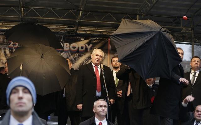 Na archívnej snímke členovia ochranky dáždnikmi chránia českého prezidenta Miloša Zemana (v strede)