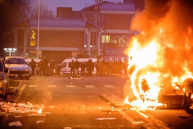 Na snímke auto horí počas demonštrácie