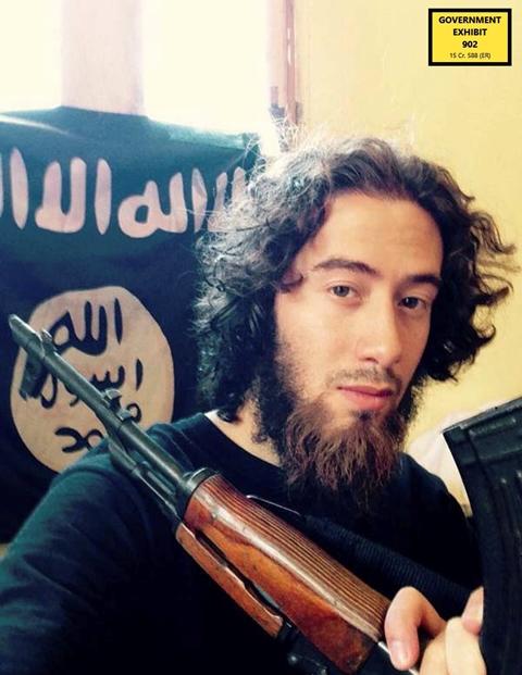 Na nedatovanej snímke Samy el-Goarany pózuje so zbraňou a zástavou organizácie Islamský štát (IS)