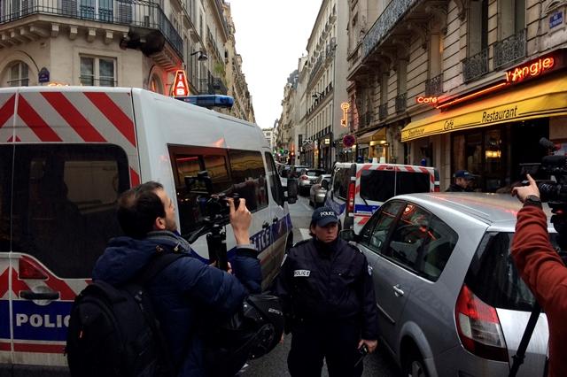 Na snímke policajný dôstojník uzatvára ulicu, kde ozbrojení policajti prehliadajú domy v okolí  múzea Louvre v Paríži