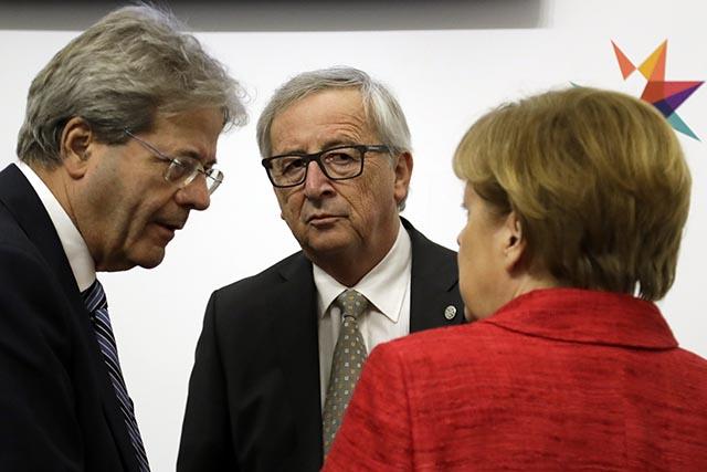 Nemecká kancelárka Angela Merkelová (vpravo) sa rozpráva s predsedom Európskej komisie Jeanom-Claudeom Junckerom (v strede) a talianskym premiérom Paolom Gentilonim (vľavo)