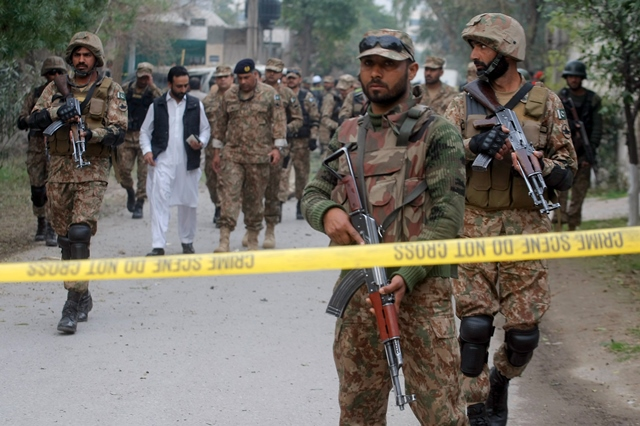 Na snímke členovia armády stoja pred policajnou páskou na mieste výbuchu
