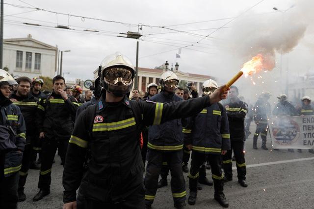 Na snímke grécky hasič so svetlicou v ruke počas protestu stoviek kolegov v centre gréckej metropoly Atén