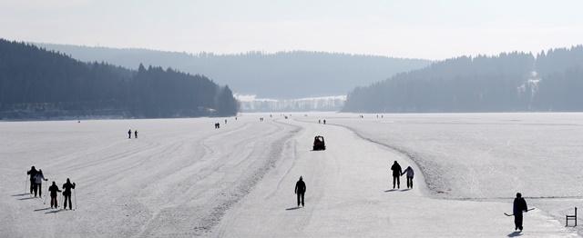 Ľudia sa korčuľujú na upravenej ploche pre korčuliarov na zamrznutej priehrade Lipno neďaleko juhočeskej obce Frymburk
