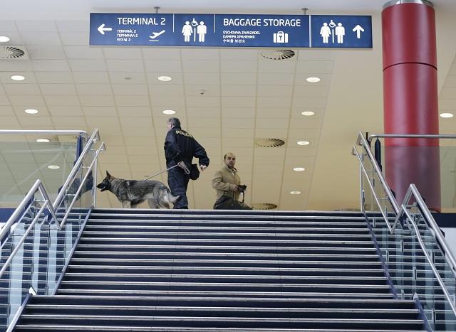 Príslušník českej polície so špeciálne vycvičeným psom na vyhľadávenie výbušnín hliadkuje na letisku Václava Havla v Prahe
