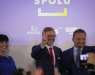Líder koalície SPOLU Petr Fiala (uprostred) ukazuje znak víťazstva po parlamentných voľbách 9. októbra 2021 v Prahe